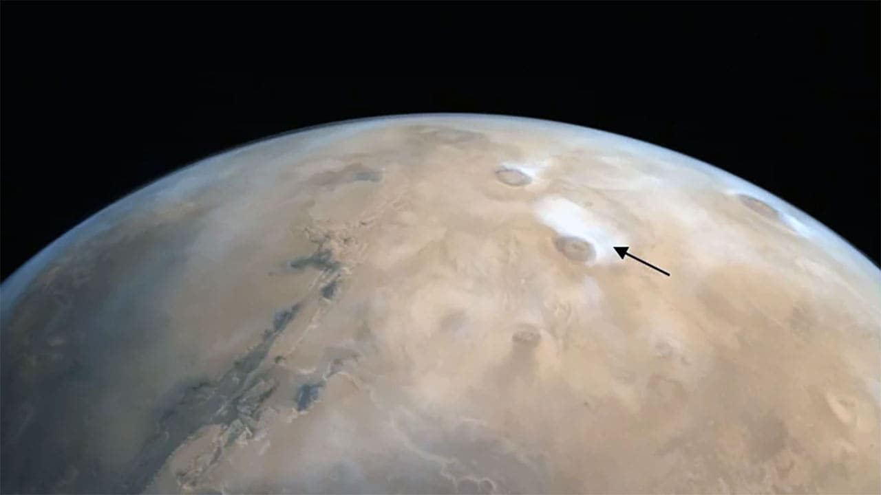 Volcanoes on Mars imaged by MOM. The arrow points at a cloud formation around the summit. Image: ISRO.