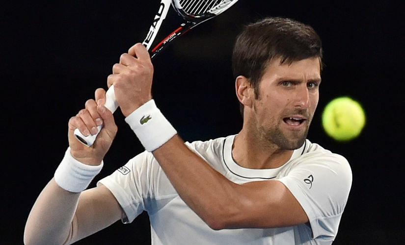 Serbia's Novak Djokovic hits a return during a practice session ahead of the Australian Open tennis tournament in Melbourne on January 13, 2018. / AFP PHOTO / PAUL CROCK / -- IMAGE RESTRICTED TO EDITORIAL USE - STRICTLY NO COMMERCIAL USE --