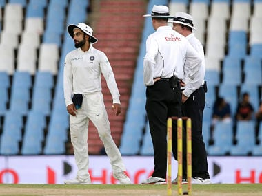 Indian Captain Virat Kohli (L) reacts as umpires suspend play due to bad light during the third day of the second Test cricket match between South Africa and India at Supersport cricket ground on January 15, 2018 in Centurion, South Africa. / AFP PHOTO / GIANLUIGI GUERCIA