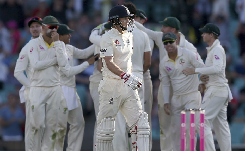 England's Joe Root, center, walks off after he was caught out against Australia. AP