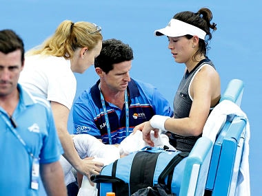 Garbine Muguruza of Spain is treated by medical staff during her match against Aleksandra Krunic of Serbia at the Brisbane International tennis tournament in Brisbane, Australia, Tuesday, Jan. 2, 2018. Muguruza fell to the court behind the baseline in the third set before retiring from her opening match. (AP Photo/Tertius Pickard)