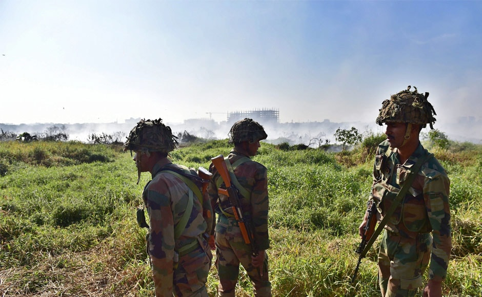 Army jawans stand guard near the Bellandur lake, after it caught fire, on Saturday. The locals had noticed huge clouds of smoke billowing from the lake replete with sewage, chemical effluents and construction debris. PTI