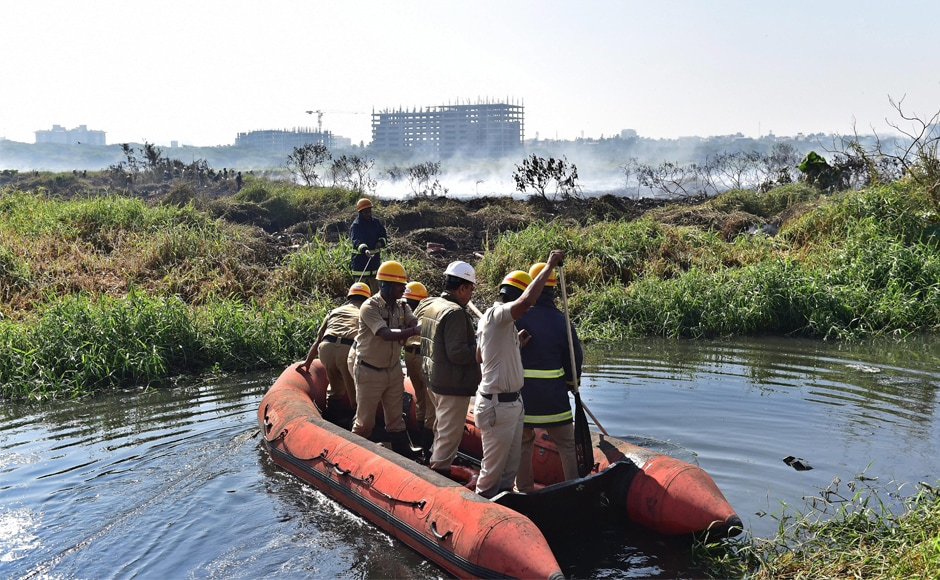 Firefighters inspect Bellandur lake on Saturday. Bengaluru mayor R Sampath Raj said the fire seems to be an outcome of the accumulation of chemicals. PTI