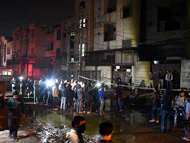 Fire fighters and media outside the two-storey cracker factory which caught fire in north Delhi's Bawana Industrial Area on Saturday. PTI