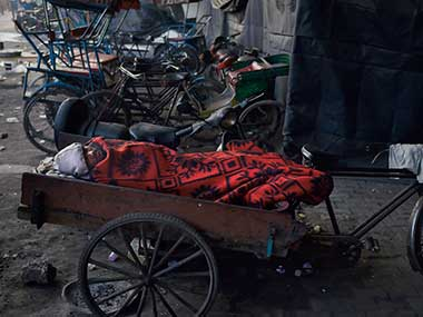 A man wrapped in a blanket sleeps on a rickshaw during a cold winter morning in Delhi. PTI