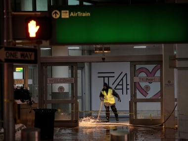 A worker at New York's JFK airport tries to dry off the water. Reuters