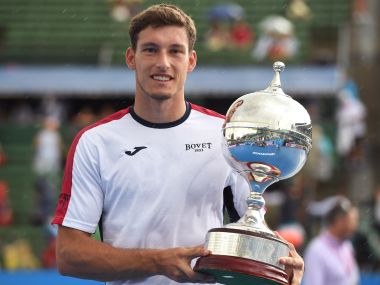 Pablo Carreno Busta of Spain holds the trophy after defeating Matthew Ebden of Australia in the final of the Kooyong Classic tennis tournament in Melbourne. AFP