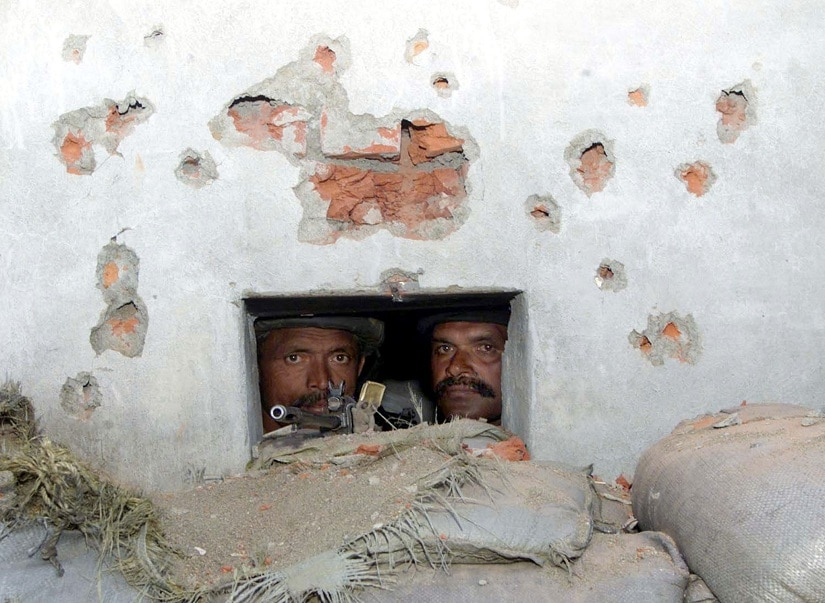 Indian soldiers look out from a bunker covered with bullet holes after an attack outside an Indian military airfield at Quil, near Srinagar in the northern Indian state of Jammu and Kashmir, October 22, 2001. Indian airforce authorities said that six people including four separatist militants were killed when militants tried to storm their military airfield on Monday. Lashkar-e-Taiba, a Pakistan based militant organisation claimed responsibility for the attack. REUTERS/Fayaz Kabli FK/DL - RP2DRIPQJJAA