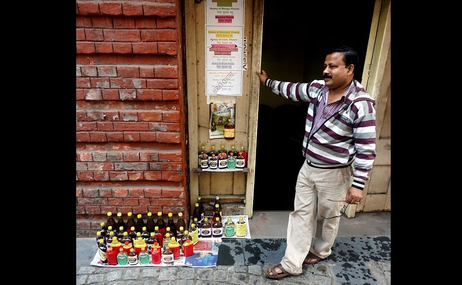 A vendor displaying organic honey at his little shop set up by  the 17th century Writers' Building, one of nearly 3,00,000 city structures dating back to Britain's rule over India. Image from AP