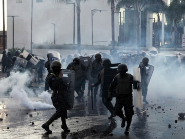 Military police stand amid tear gas as they clash with supporters of opposition presidential candidate Salvador Nasralla near the presidential house in Tegucigalpa, Honduras, Friday, Jan. 12, 2018. AP