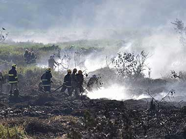 Firefighters douse the fire in Bellandur lake in Bengaluru on Saturday. PTI