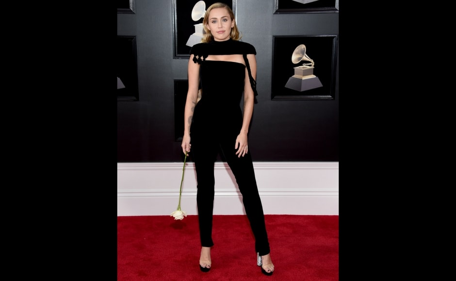 Miley Cyrus holds a white rose as she arrives at the 60th annual Grammy Awards. AP/Evan Agostini