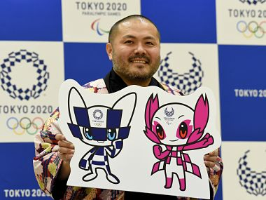 "Ryo Taniguchi, winning designer of the official mascots for the 2020 Olympics (L) and Paralympics Games, poses for photographers at an elementary school in Tokyo on February 28, 2018. Tokyo on February 28 unveiled its long-awaited mascot for the 2020 Olympic Games: a futuristic blue-checked, doe-eyed character with pointy ears and ""special powers"" that was picked by schoolchildren across mascot-mad Japan. / AFP PHOTO / TORU YAMANAKA"