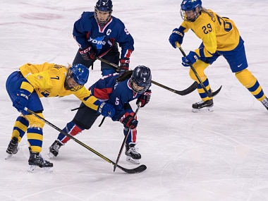 Unified Korea's Caroline Nancy Park (front R) clashes with Sweden's Johanna Olofsson (L), as Unified Korea's Park Jongah (back L) and Sweden's Olivia Carlsson watch, during the women's preliminary round ice hockey match between Sweden and Unified Korea during the Pyeongchang 2018 Winter Olympic Games at the Kwandong Hockey Centre in Gangneung on February 12, 2018. / AFP PHOTO / Ed JONES