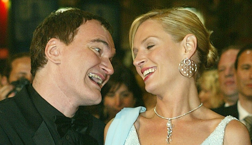 """American director Quentin Tarantino jokes with his actress Uma Thurman as they arrive at the festival palace to attend the screening of their film """"Kill Bill Vol.2"""" being shown out of competition at the 57th International film festival in Cannes, southern France, Sunday, May 16, 2004. Tarantino heads the jury of the 57th international film festival. (AP Photo/Laurent Rebours)"""
