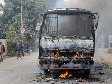 Angry students of Allahabad Central University set ablaze a city bus during a protest against brutal murder of a Law student, in Allahabad. PTI