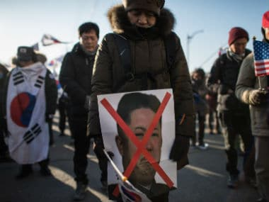 An anti-North Korean protester holds a picture of North Korean leader Kim Jong-Un. AFP