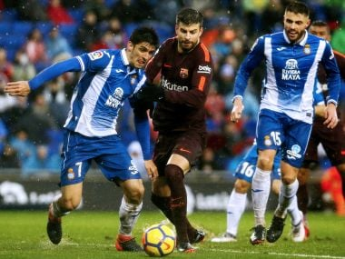Barcelona's Gerard Pique (centre) vies with Espanyol players during a La Liga match on Sunday. AFP