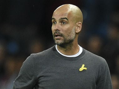 Manchester City's Spanish manager Pep Guardiola watches from the touchline wearing a yellow ribbon, a symbol used by Catalan separatists in Spain. AFP