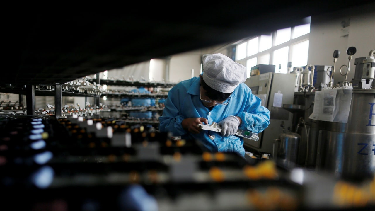 A labourer works inside an electronics factory in Qingdao, China. Reuters