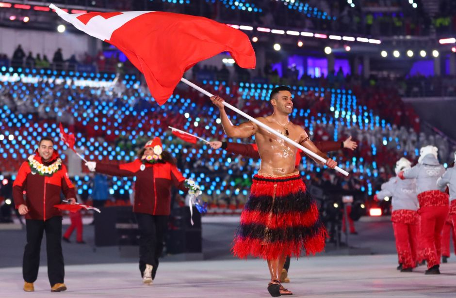 Pita Taufatofua of Tonga carries the national flag with delegates. One of the biggest cheers was reserved for muscle-bound Tongan Taufatofua, who repeated his famed Rio Games entrance by marching in shirtless, oiled up and wearing a traditional skirt -- this time in sub-zero temperatures. Reuters
