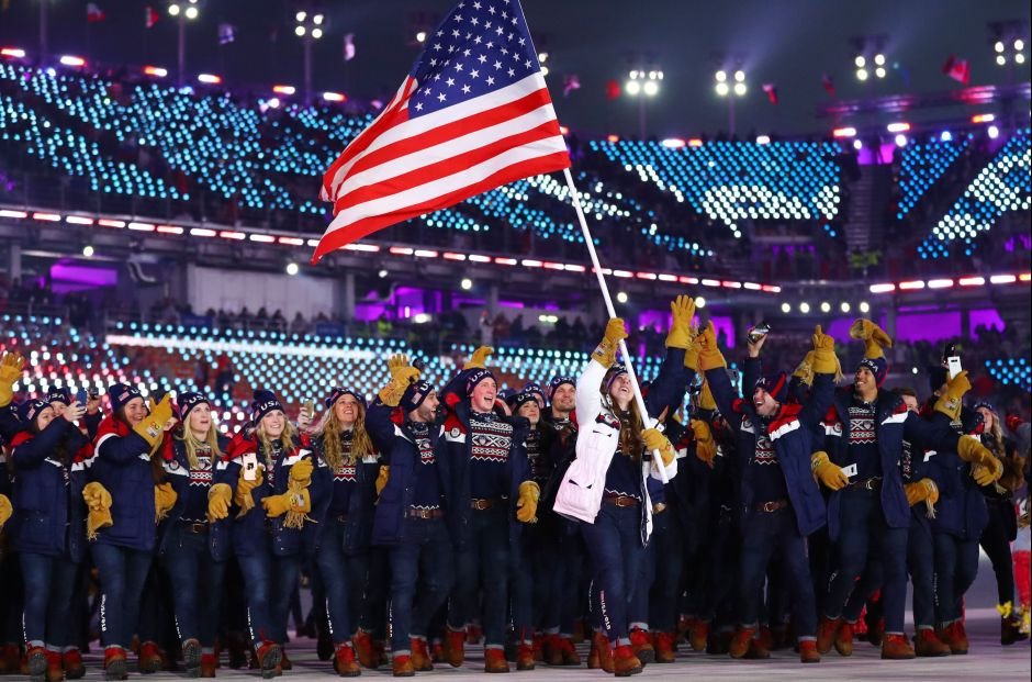 Erin Hamlin of US carries the national flag with delegates during the opening ceremony. When the American athletes walked in, the Korean pop hit Gangnam Style blared around the stadium, sparking the 'Horse Dance' in the crowd and among the volunteers. Reuters