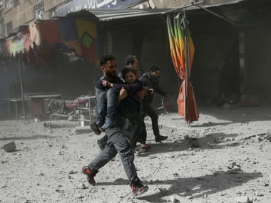 A man runs as he holds a girl after an airstrike in the besieged town of Douma in eastern Ghouta in Damascus, Syria. Reuters