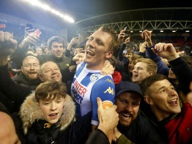 Wigan Athletic's Dan Burn celebrates with fans on the pitch after the win over Manchester City. Reuters