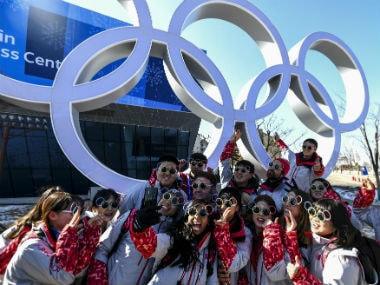 Volunteers pose for a photo next next to the Olympics rings ahead of the Winter Olympics 2018 in Pyeongchang. AFP