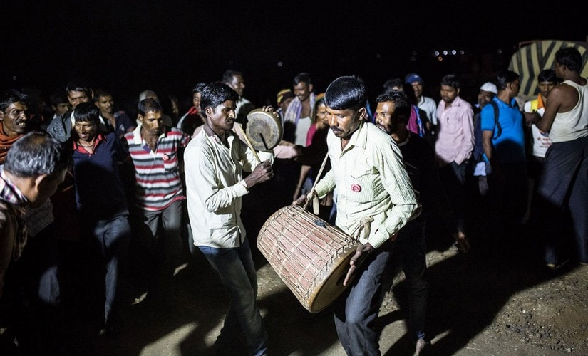 After a long day of walking, some farmers sing and dance at night; others like Waghere are exhausted; soon, everyone rests for the night under the open sky. Image courtesy: PARI