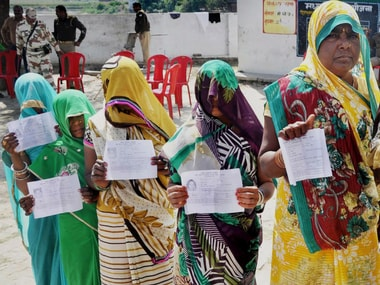 Voters display their voter's ID card at a polling booth for Phulpur bypoll elections in Allahabad on Sunday. PTI