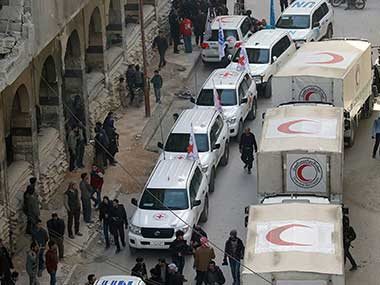 Civilians gathering near a convoy of vehicles of the Syrian Red Crescent in Douma, Eastern Ghouta. AP