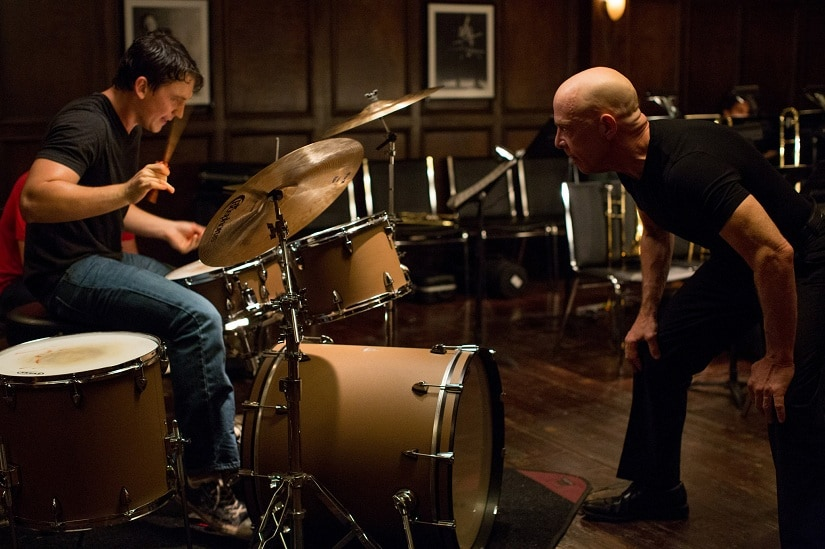 Terence Fletcher (JK Simmons) pushes an aspiring jazz drummer, Andrew Neyman (Miles Teller), past his physical and mental limits in Whiplash.