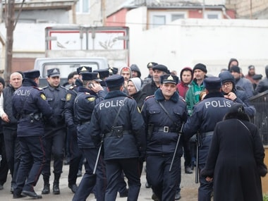 Police officers gather near a drug abuse treatment center that caught fire in Baku, Azerbaijan. Reuters
