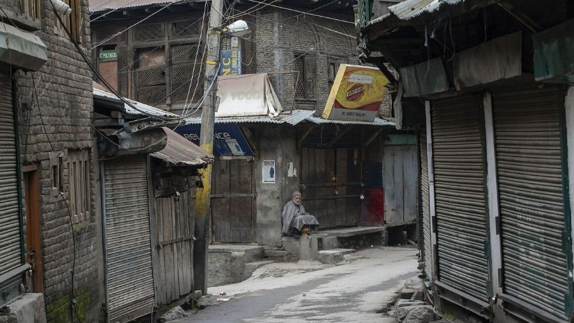 An elderly Kashmiri man sits outside a closed market during a strike in Srinagar, Indian controlled Kashmir, Feb. 17, 2019. The image was part of a series of photographs by Associated Press photographers which won the 2020 Pulitzer Prize for Feature Photography. Image via The Associated Press/ Dar Yasin