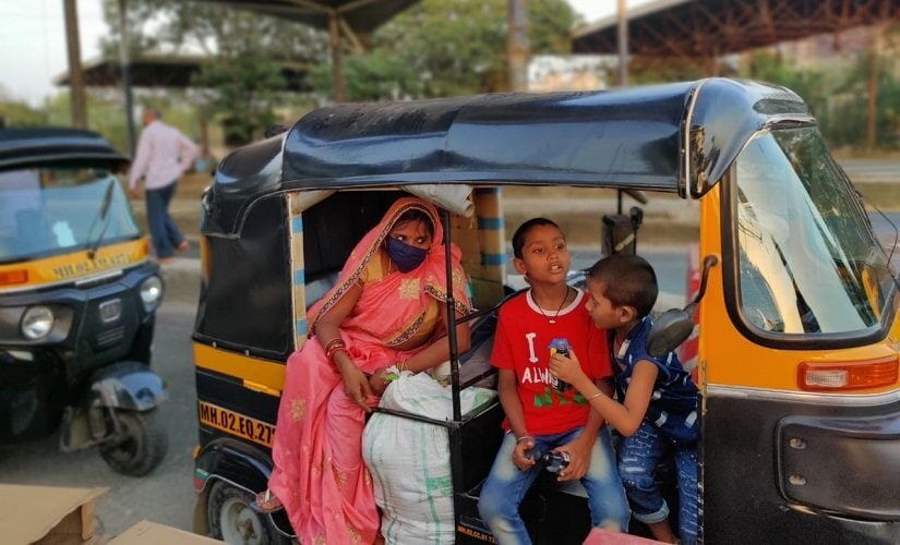 Vidyanand's wife Rekha with her two children wait in the auto at the Kharegaon checkpost. Image/Parth MN