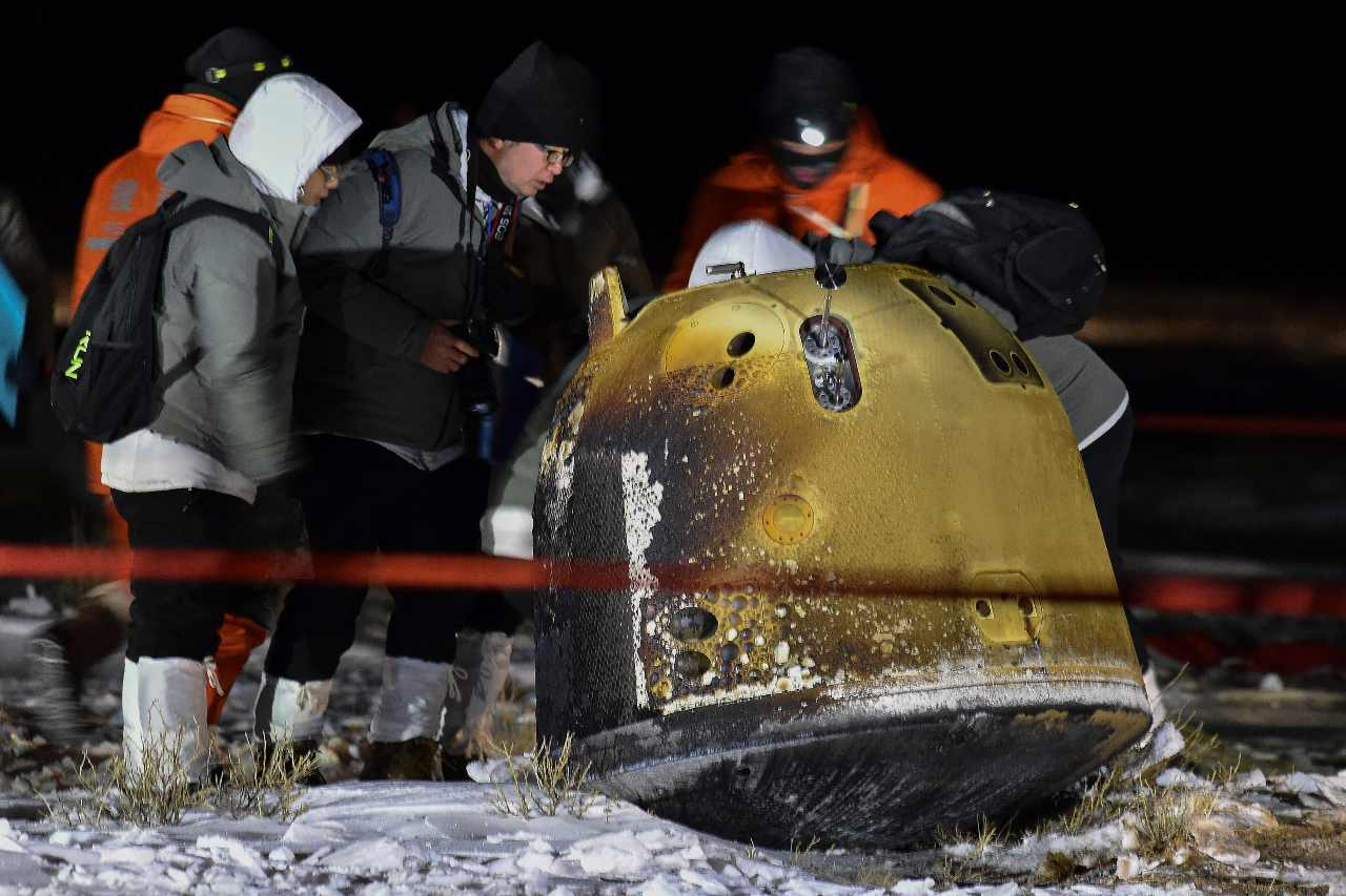 In this photo released by Xinhua News Agency, crew members check on the capsule of the Chang'e 5 probe after its successful landed in Siziwang Banner, north China's Inner Mongolia Autonomous Region on Thursday, Dec. 17, 2020. A Chinese lunar capsule returned to Earth on Thursday with the first fresh samples of rock and debris from the moon in more than 40 years. (Ren Junchuan/Xinhua via AP)