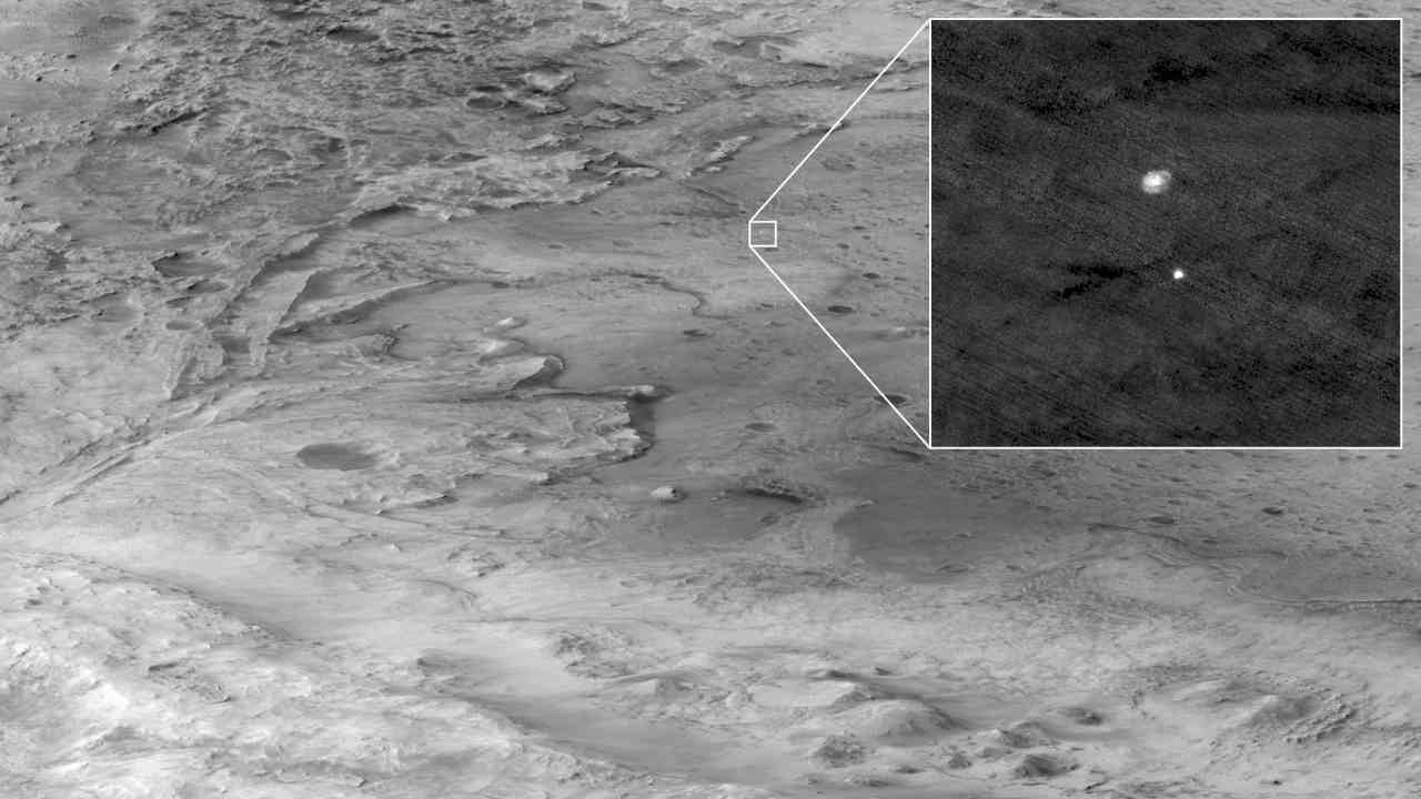 The descent stage holding Percy can be seen falling through the Martian atmosphere, its parachute trailing behind, in this 18 Feb image taken by HiRISE. Image: NASA