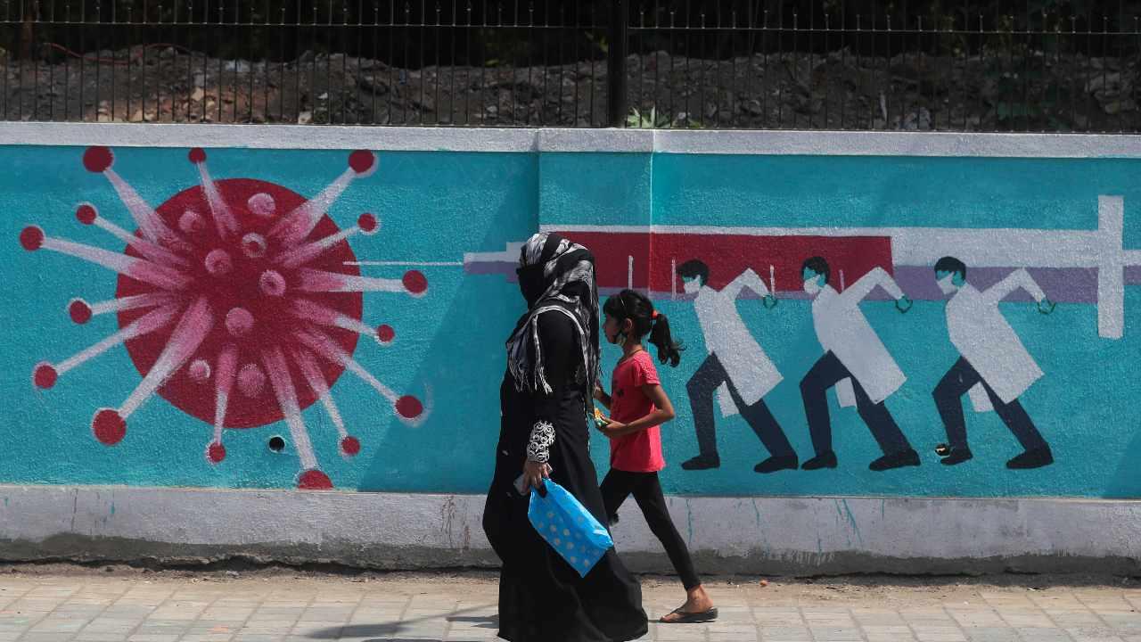 A woman along with a girl walk past a graffiti, depicting the coronavirus in Mumbai, India. Image credit: AP Photo/Rafiq Maqbool