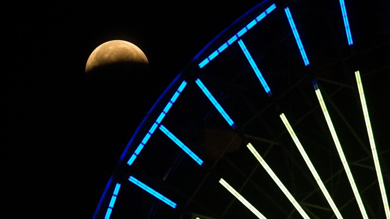 The first total lunar eclipse in more than two years coincided with a supermoon for a cosmic show and here it can be seen behind a ferris wheel in California, USA. (AP Photo/Ringo H.W. Chiu)