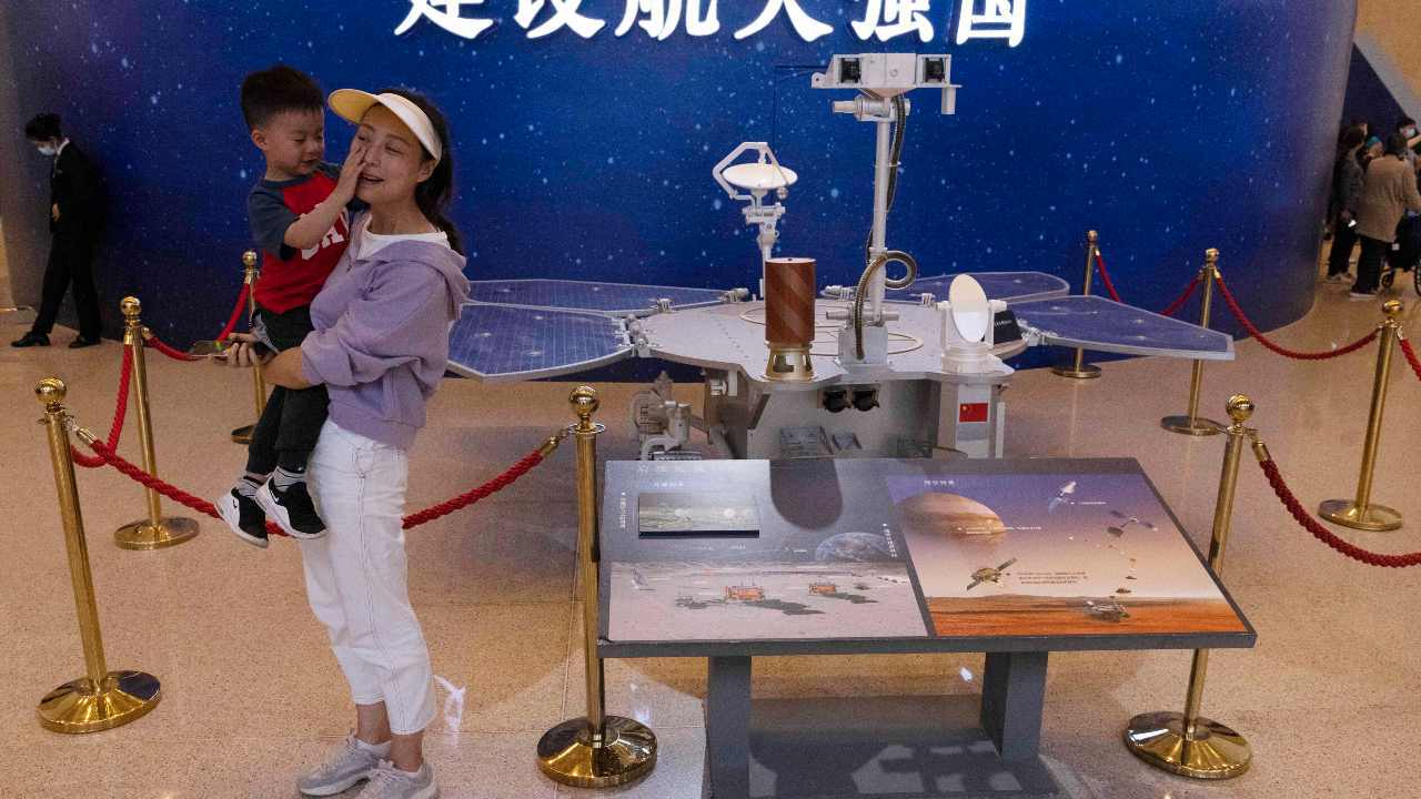 People stand next to a life size model of the Chinese Mars rover at an exhibition on China's space program. The Mars rover Zhurong is named after the Chinese god of fire. Image credit: AP Photo/Ng Han Guan