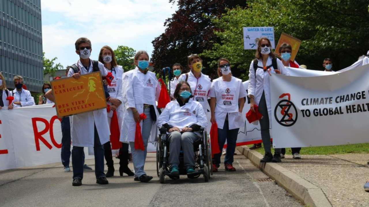 Around two hundred people wearing white medical coats and facemasks marched or were pushed in wheelchairs two kilometres (1.2 miles) through Geneva's international district to the WHO headquarters Image credit: Extinction Rebellion