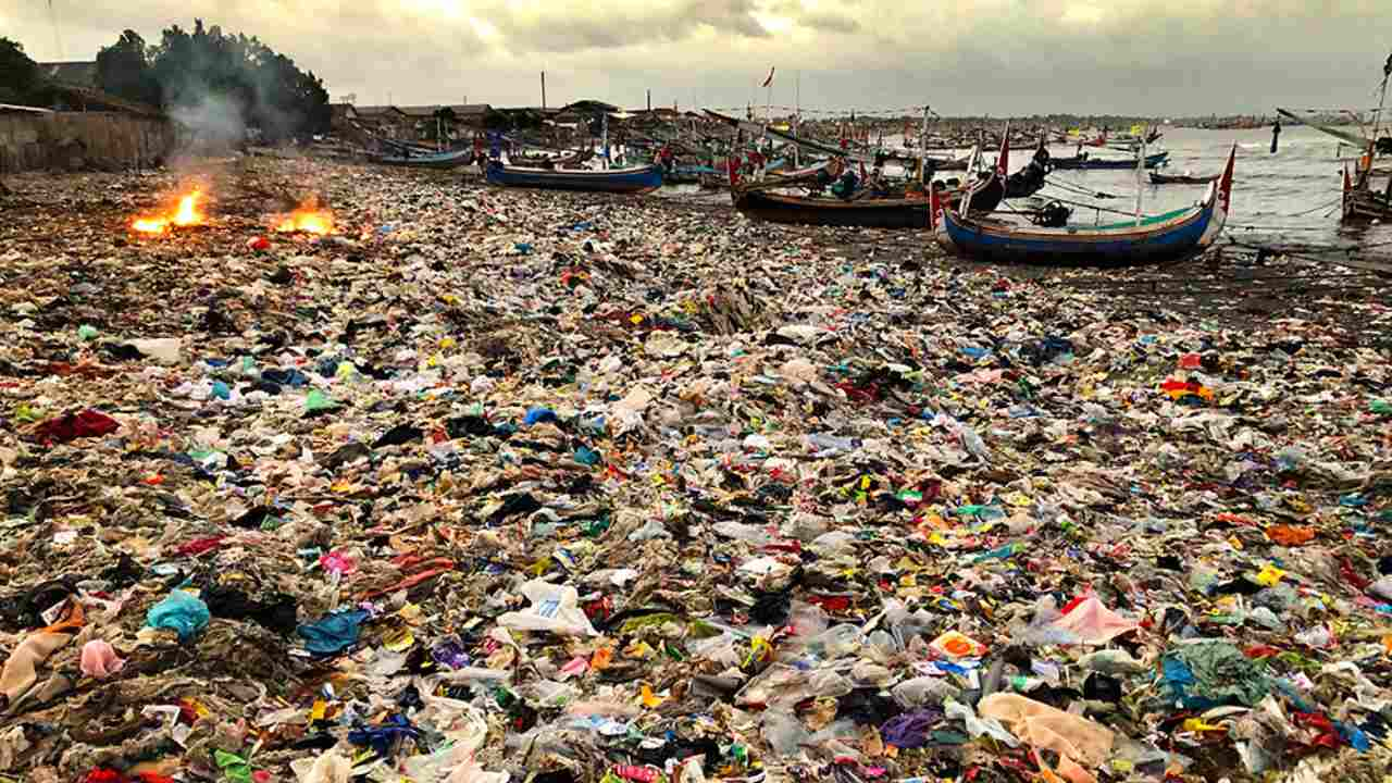 This local beach in Java, Indonesia, has become an illegal dumpsite for plastic waste. One of the residents can be seen burning the plastic, so it doesn't enter her house at high tide. Photo by Vincent Kneefel (The Netherlands)