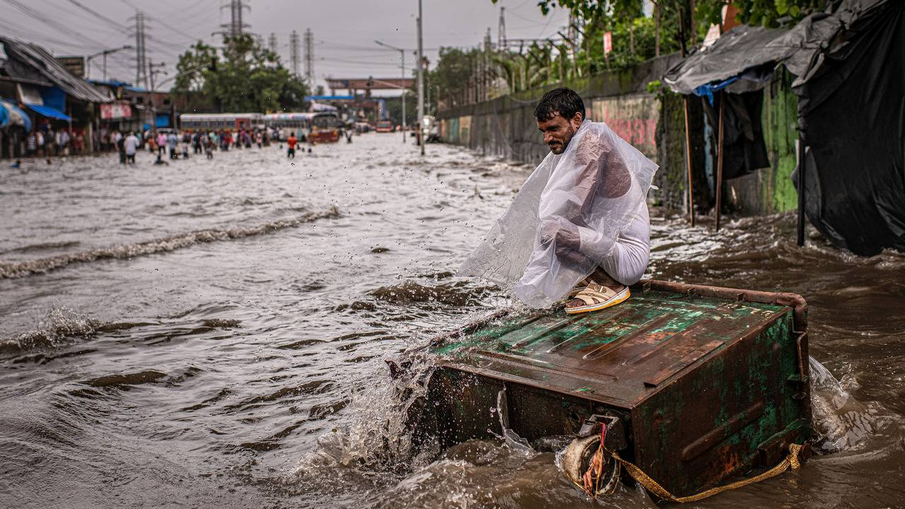 A resident sits on top of a dumpster surrounded by flood waters in the Scion neighborhood, along the Mithi River, of Mumbai, India, Aug. 4, 2019.  By Bryan Denton c.2019 The New York Times