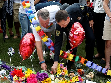 Orlando mayor Buddy Dyer (L) and Chief of Police John Mina lay flowers at a memorial service the day after the mass shooting at Pulse. Reuters