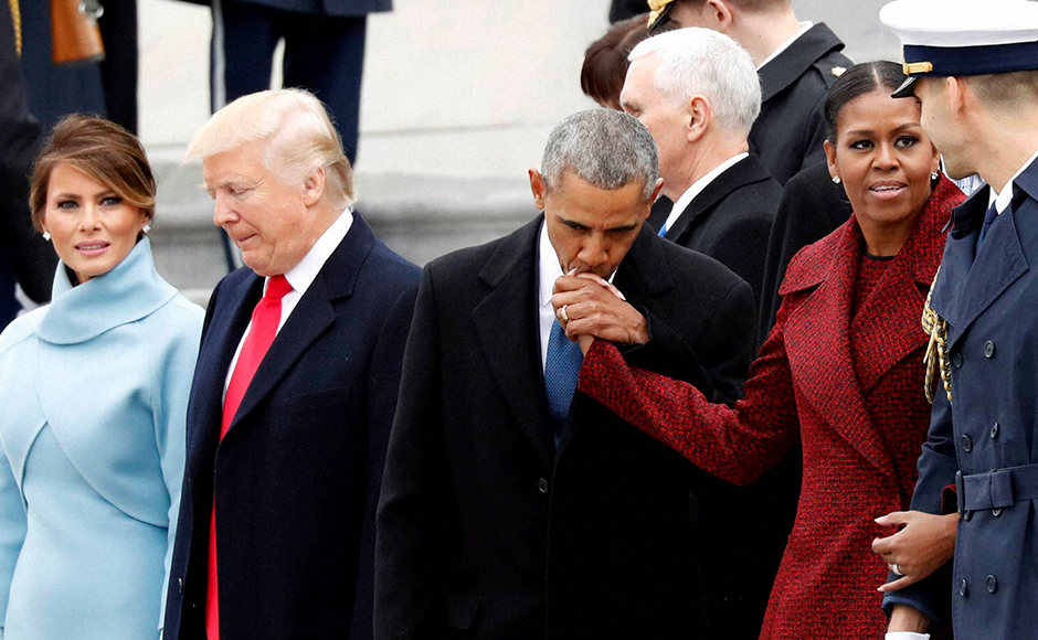 Barack Obama kisses Michelle Obama's hand during a departure ceremony on the East Front of the U.S. Capitol. AP