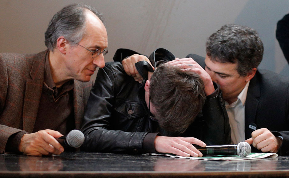 The new chief editor of French satirical magazine Charlie Hebdo, Gerard Biard, left, and columnist Patrick Pelloux, right, comfort cartoonist Luz during a press conference in Paris, France, Tuesday, Jan. 13, 2015. Twelve people died when two masked gunmen assaulted the newspaper's offices on Jan. 7, including much of the editorial staff and two police. It was the beginning of three days of terror around Paris that saw 17 people killed before the three Islamic extremist attackers were gunned down by security forces. Charlie Hebdo had faced repeated threats for depictions of the prophet, and its editor and his police bodyguard were the first to die. AP