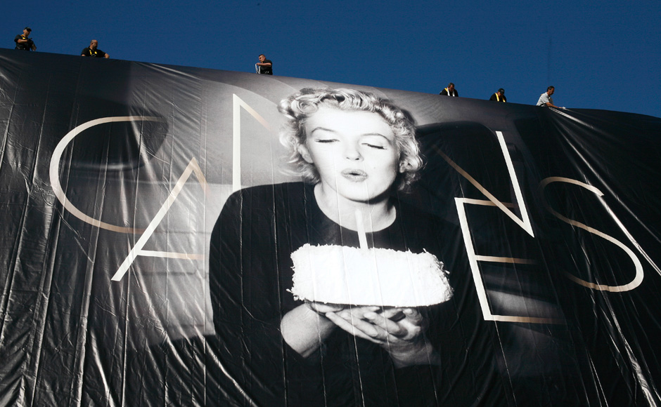 Workers sets up a giant 65th Cannes Film Festival official poster showing Marilyn Monroe on the Cannes Festival Palace. AP
