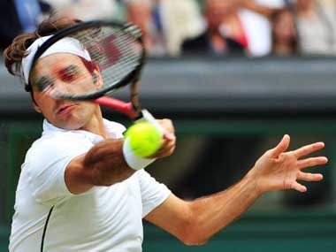 Roger Federer returns the ball to French player Jo-Wilfried Tsonga during the men's single quarter final at the Wimbledon Tennis Championships at the All England Tennis Club, London.