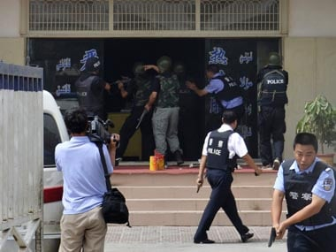 """A handout picture shows armed policemen trying to rescue hostages at a police station during a clash in Hotan, Xinjiang Uygur Autonomous Region July 18, 2011. China on Wednesday raised the death toll to 18 from the clash at the police station in the restive far western region of Xinjiang, saying that 14 """"rioters"""" died along with two policemen and two hostages in the worst violence there in a year.   Xinjiang Public Security Bureau/Handout/Reuters."""